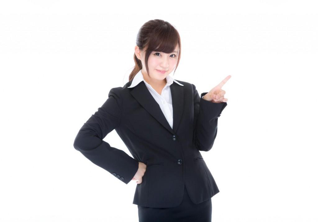 指差しポーズをするスーツ姿の女性