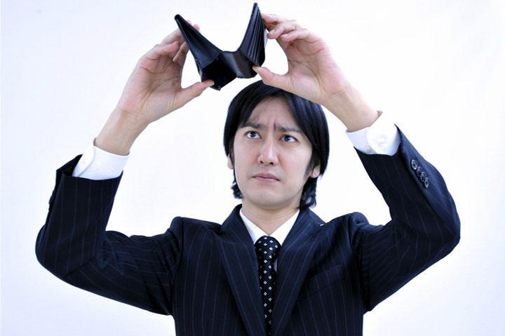 空っぽの財布とスーツ姿の男性