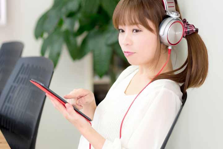 ヘッドフォンをしながらタブレットを操作する女性