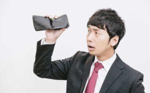 空っぽの財布を持つ男性